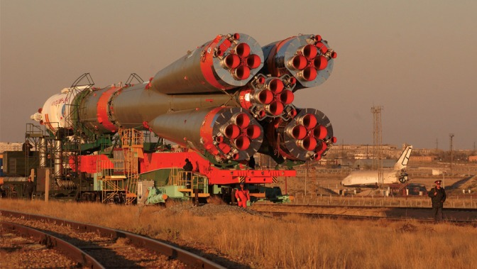"With a mockup of the defunct Russian ""Buran"" Space Shuttle sitting passively nearby (lower right), the Soyuz TMA-3 spacecraft and its booster rocket crawl on a rail car to the launch pad at the Baikonur Cosmodrome, Kazakhstan October 16, 2003, in preparation for its liftoff October 18 to carry three astronauts to the International Space Station. (NASA/Bill Ingalls)"